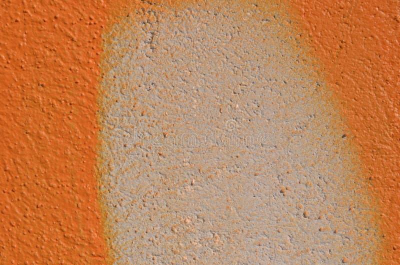 Orange graffiti on wall. Textured wall airbrushed by orange and white graffiti paint royalty free stock photo