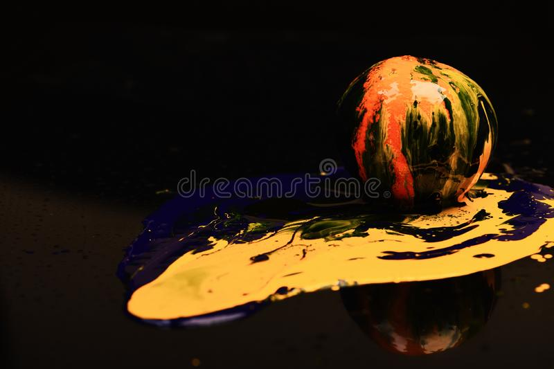 Orange or grapefruit covered with paints, copy space. Paint splashing on orange fruit. Drops of blue and yellow oil or acrylic paint poured on fruit on black royalty free stock images