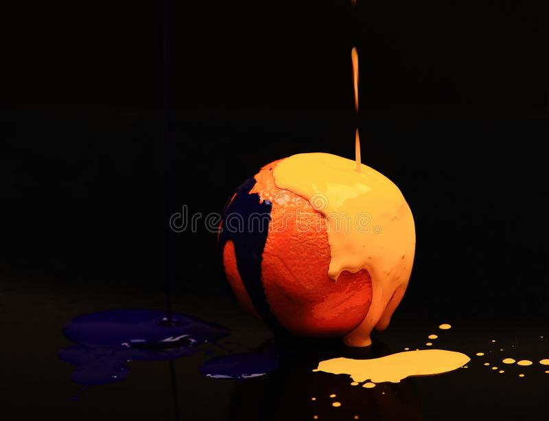 Orange or grapefruit covered with paints. Nutrition and food art. Concept. Paint splashing on orange fruit. Drops of blue and yellow oil or acrylic paint poured royalty free stock photo