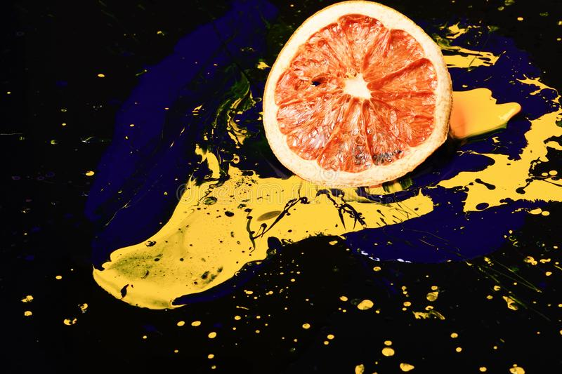 Orange or grapefruit half covered with paints. Paint splashing on grapefruit fruit. Nutrition and food art concept. Drops of blue and yellow oil or acrylic royalty free stock photos