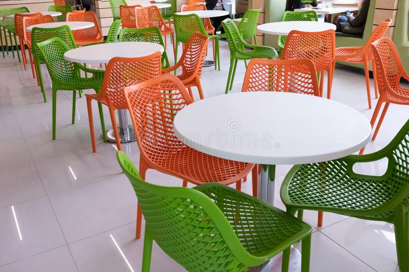 Orange and green chairs around white tables. A modern interior of food court in a mall, cafe, airport or family fast food stock photography