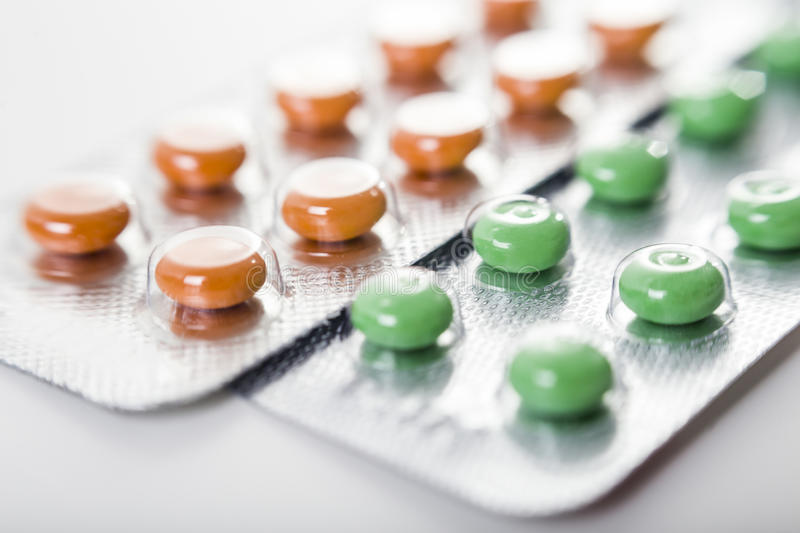 Orange and green pills stock images