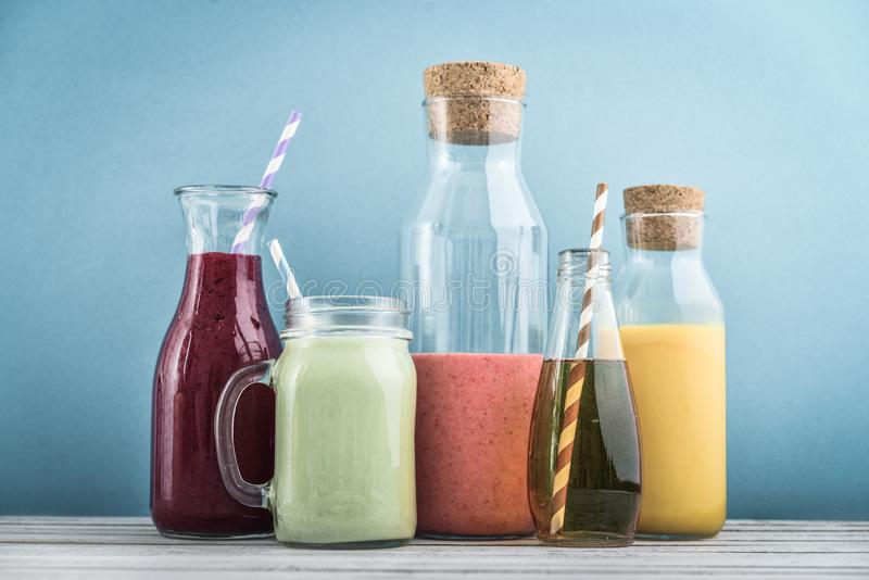 Orange, green and red colored smoothies. And juice in a glass jars on a blue background royalty free stock photos