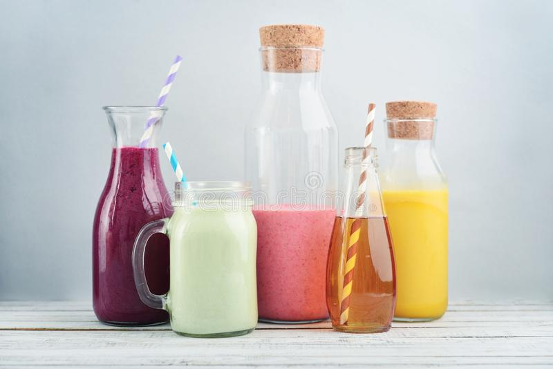 Orange, green and red colored smoothies. And juice in a glass jars on a blue background royalty free stock image