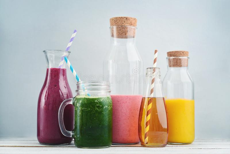 Orange, green and red colored smoothies. And juice in a glass jars on a blue background royalty free stock photo