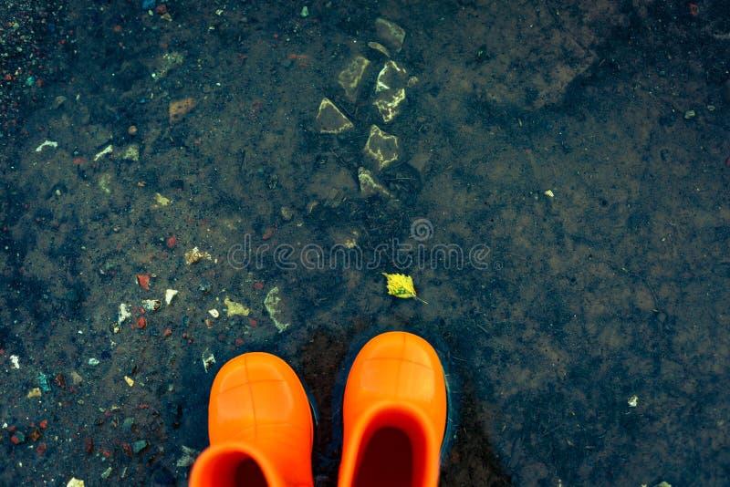 Orange gummistöveler som står i en pöl arkivbild