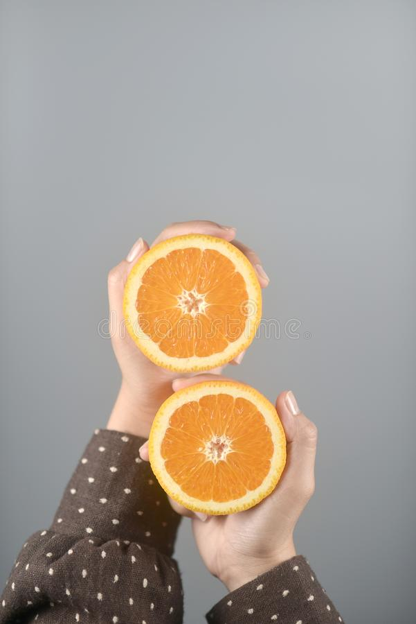 Orange half cut 2 pieces on women hands with brown coat on light grey background.vertical image. Orange half cut 2 pieces on women hands with brown coat on light stock photo