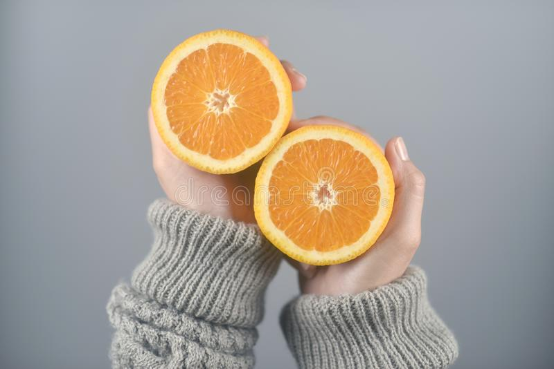 Orange half cut 2 pieces on women hands with sweater on light grey background. horizontal image. Beautiful, bright, brown, closeup, color, concept, dessert stock image