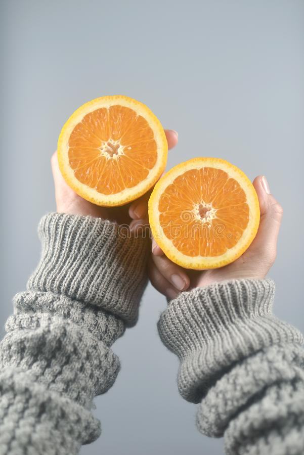 Orange half cut 2 pieces on women hands with sweater on light grey background. vertical image. Beautiful, bright, brown, closeup, color, concept, dessert, diet royalty free stock images
