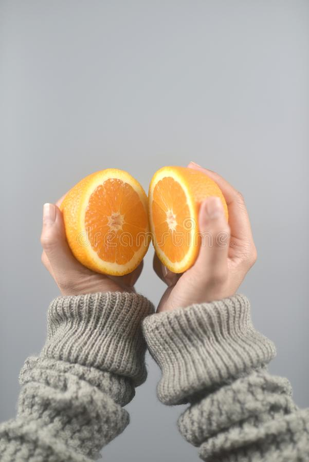 Orange half cut 2 pieces on women hands with sweater on light grey background.vertical image. Orange half cut 2 pieces on women hands with sweater on light grey royalty free stock image