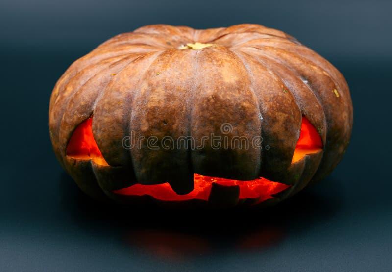Orange Halloween-Kürbis auf schwarzem Hintergrund Halloween-Parteidekor Geschnitzter Kürbis mit furchtsamem Gesicht und Rotglühen stockfotografie