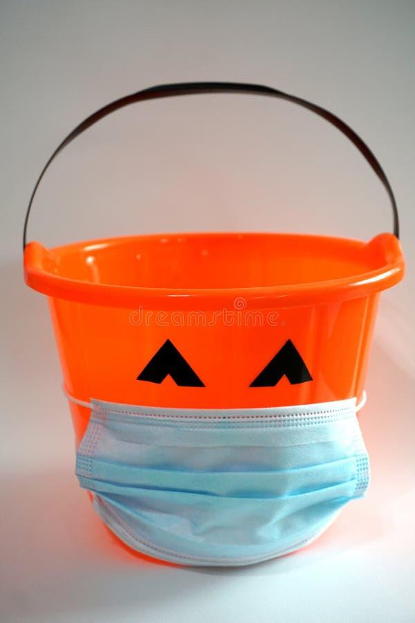 Free Orange Halloween Pumpkin Bucket Wearing A Blue Face Mask For Virus, Coronavirus, Covid-19, Pandemic Protection Stock Image - 196661691