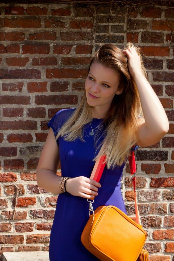 Orange handväska för blond klänning för kvinna blå, Groot Begijnhof, Leuven, Belgien arkivfoto