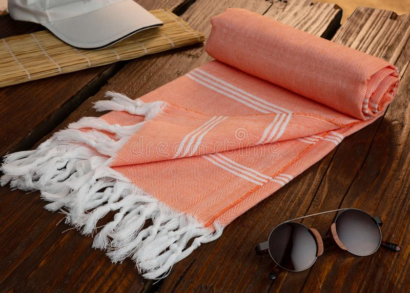 Orange Handwoven hammam Turkish cotton towel on wooden pier. With sunglasses, baseball cap and straw matt beside royalty free stock photo