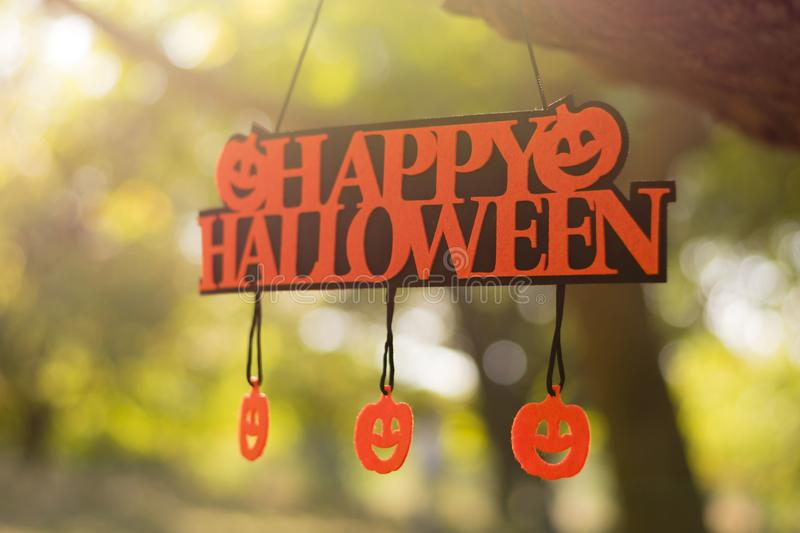 Orange `Happy Halloween` hanging on a green tree. There are smiling pumpkins on it stock image
