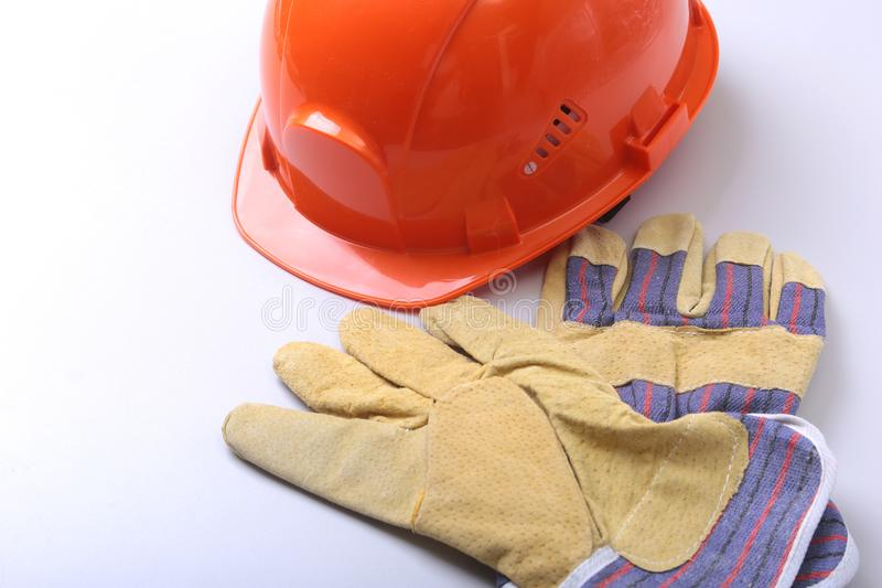 Orange hard hat, goggles and safety gloves on a white background. royalty free stock images