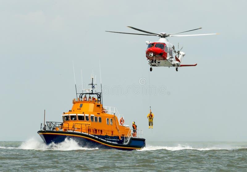 Orange havsräddningsaktionfartyg med räddningsaktionhelikoptern fotografering för bildbyråer
