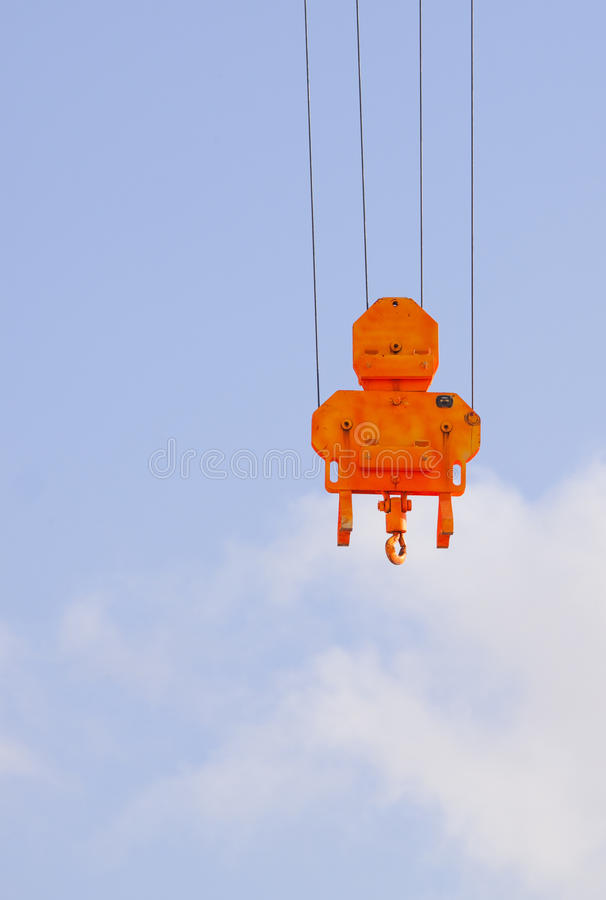 Orange heavy lift crane hook. Against a blue sky stock images