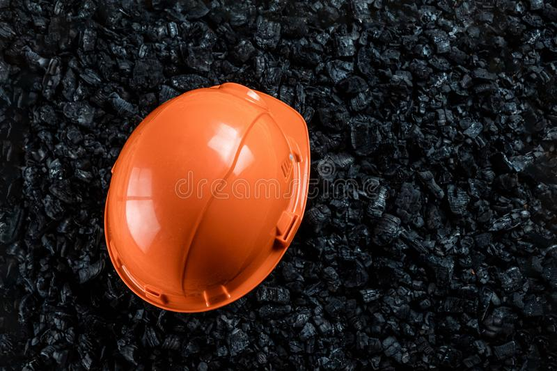 An orange helmet of a miner lies on a heap of coal, open pit coal mining, copy space. Fossil fuels, environmental pollution.  royalty free stock photo