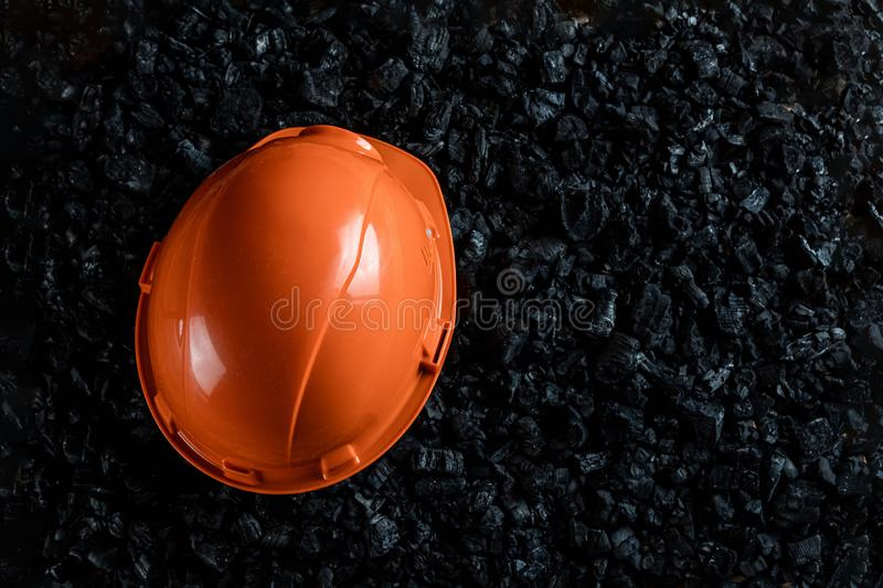 An orange helmet of a miner lies on a heap of coal, open pit coal mining, copy space. Fossil fuels, environmental pollution.  stock images