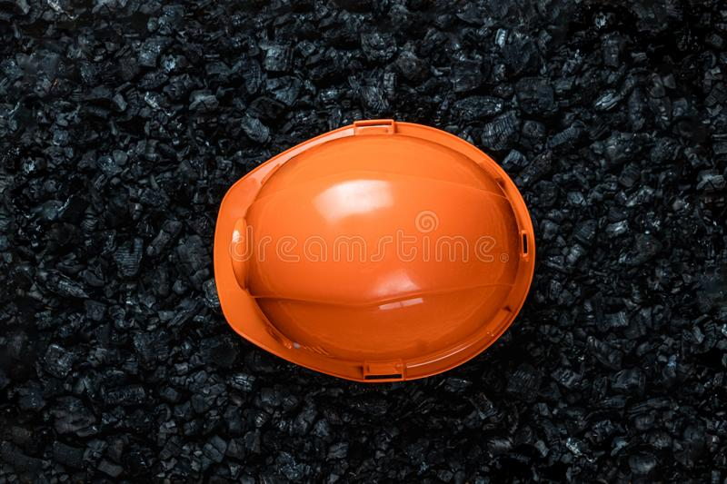 An orange helmet of a miner lies on a heap of coal, open pit coal mining, copy space. Fossil fuels, environmental pollution.  stock image