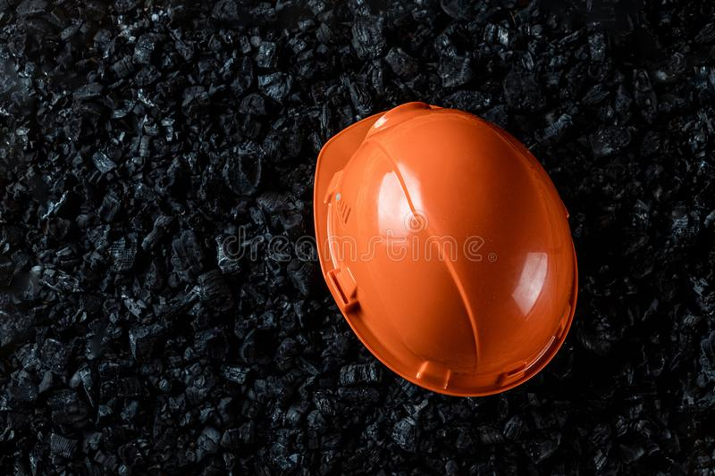 An orange helmet of a miner lies on a heap of coal, open pit coal mining, copy space. Fossil fuels, environmental pollution.  royalty free stock photos