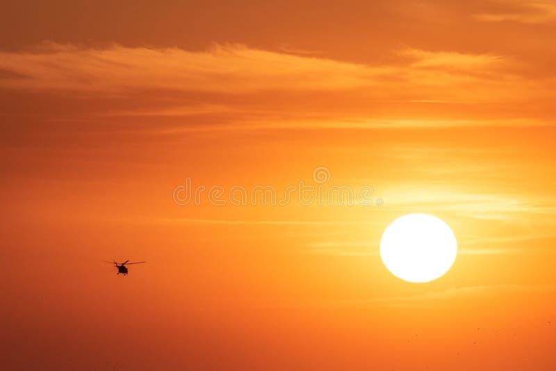 Orange himmelbakgrund för solnedgång på aftonen med moln och konturn av helikoptern royaltyfria bilder