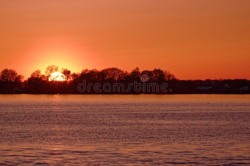 Orange Himmelsonnenuntergang auf einem See lizenzfreie stockbilder