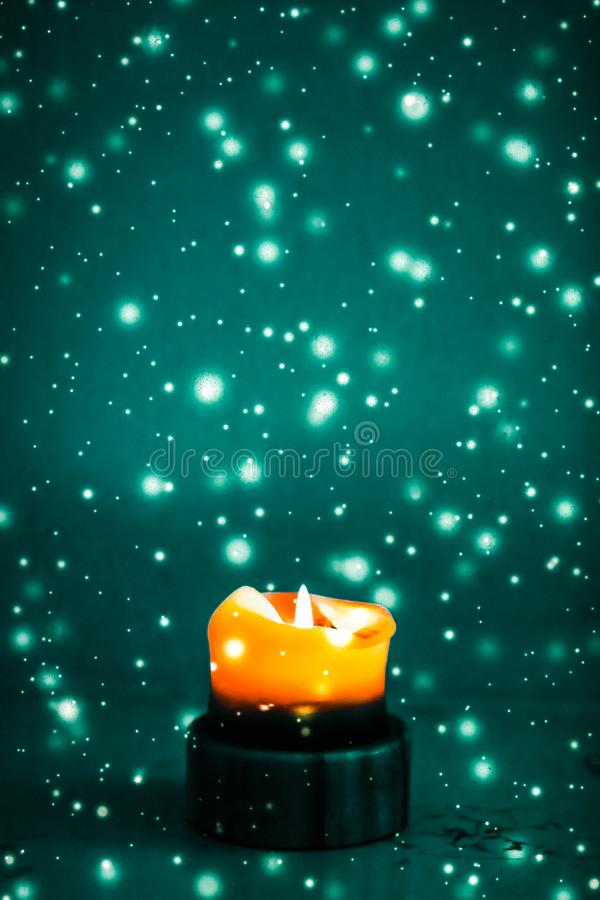 Orange holiday candle on green sparkling snowing background, luxury branding design for Halloween, New Years Eve and Christmas. Happy holidays, greeting card and royalty free stock photo
