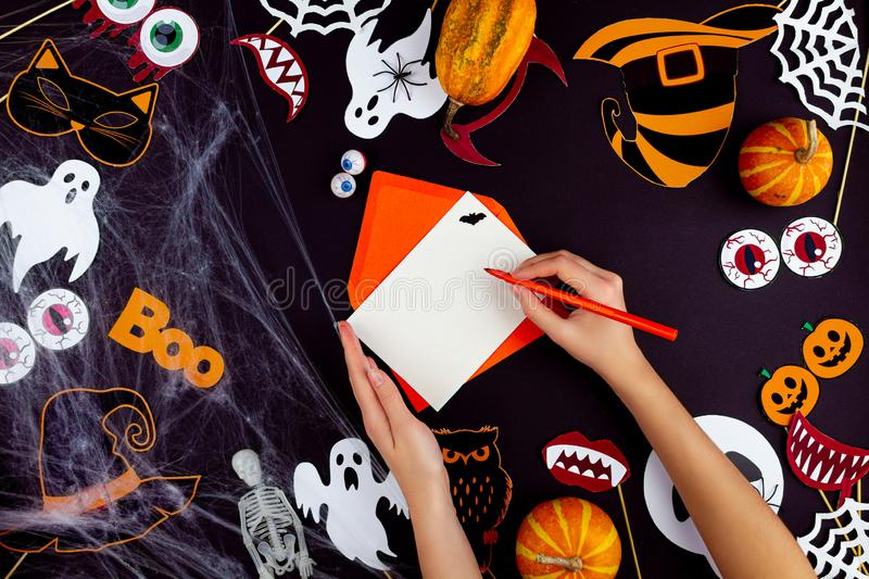 Orange holiday Halloween background with Halloween props. Female hands are writing greeting card on black background. Little pumpkins, photo props, masks, decor royalty free stock photos