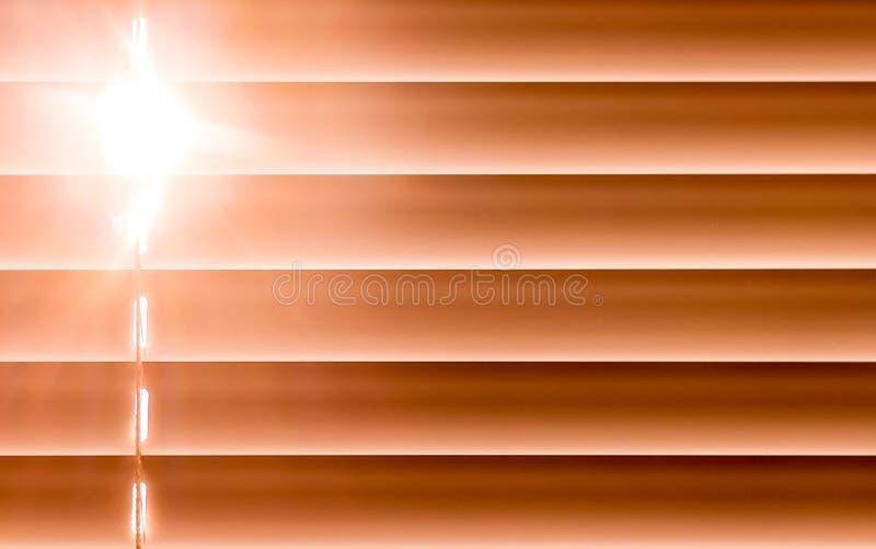 Orange horizontale Vorhänge auf dem Fenster schaffen einen Rhythmus durch t lizenzfreies stockfoto