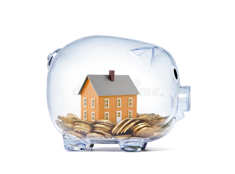 Orange house on money inside transparent piggy bank stock image