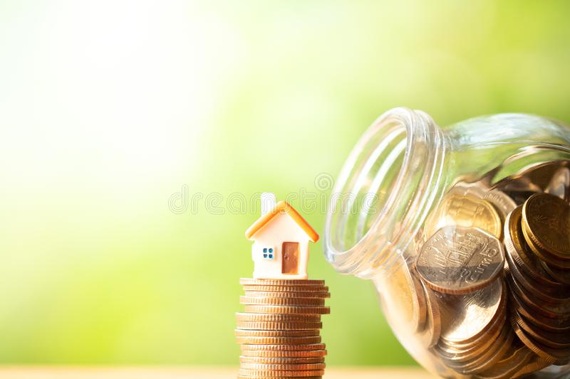 Orange house shape figure on stack and pile of coins. Beside glass jar or piggy bank on wooden table on greenery blurred background with copy space. Business stock photography