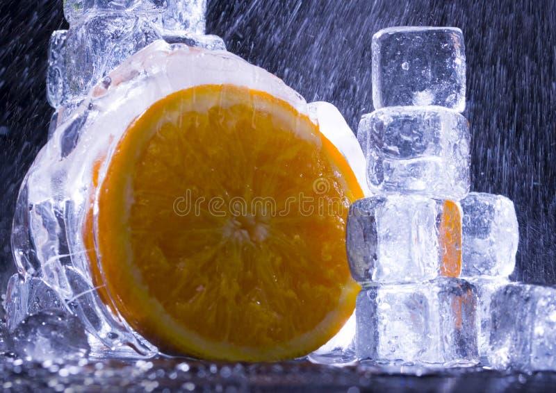 Orange with ice cubes royalty free stock photos