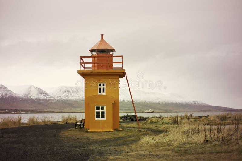 Orange Icelandic Lighthouse against mountain background royalty free stock images