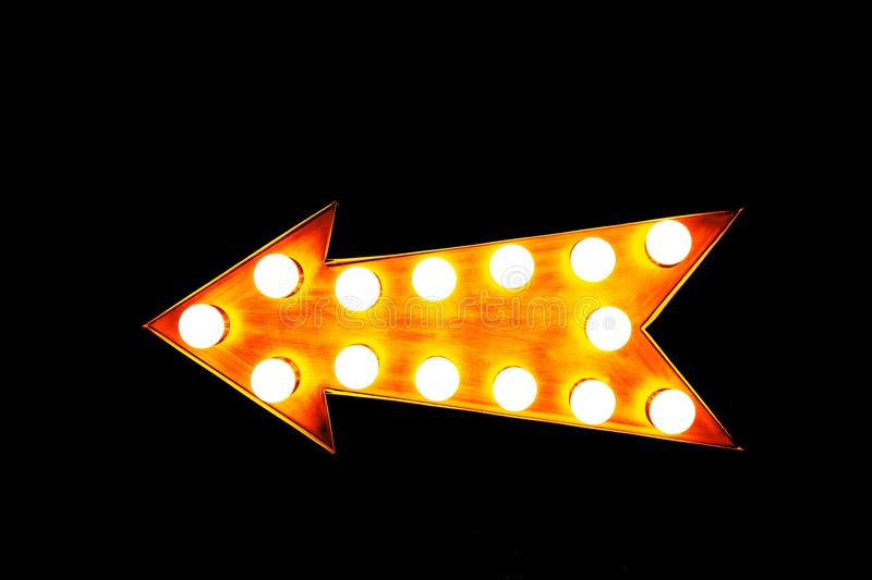 Orange illuminated display arrow sign with light bulbs against a seamless black background royalty free stock photography
