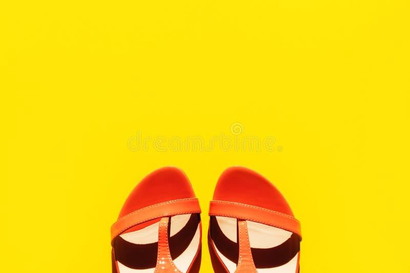 Orange innegrejkvinnors sandaler på en rosa bakgrund fotografering för bildbyråer