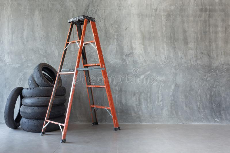 Orange iron ladder and old motorcycle tire on Bare cement wall royalty free stock photography