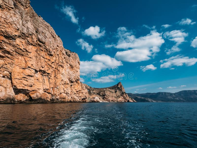 Orange island mountain coastline, blue sky with clouds and ocean water, view from boat, summer travel landscape royalty free stock photo