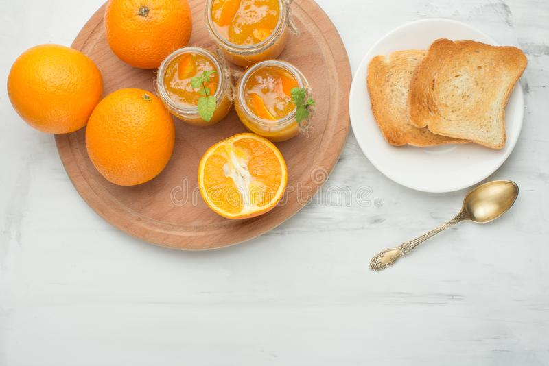 Orange jam in a glass jar on a light background with toasts. With empty space for writing stock photography