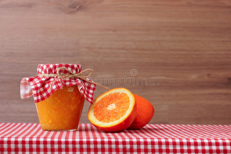 Orange jam in glass jar and orange halves on a red checkered tablecloth. Wooden background stock images
