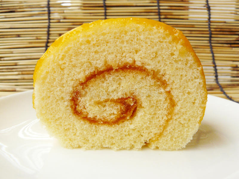 Orange jam roll cake. Close up the front view of orange jam roll cake on a white plate with mini silver stainless fork royalty free stock images