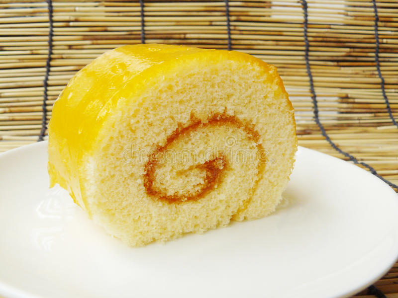 Orange jam roll cake. Close up the side view of orange jam roll cake on a white plate stock photos