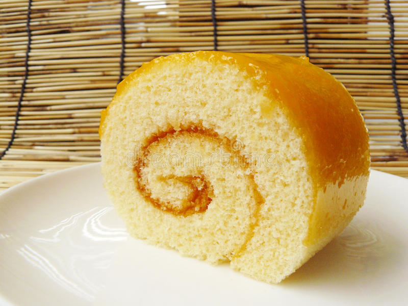 Orange jam roll cake. Close up the side view of orange jam roll cake on a white plate royalty free stock photo
