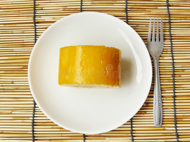 Orange jam roll cake. Close up the top view of orange jam roll cake on a white plate with mini silver stainless fork stock photos