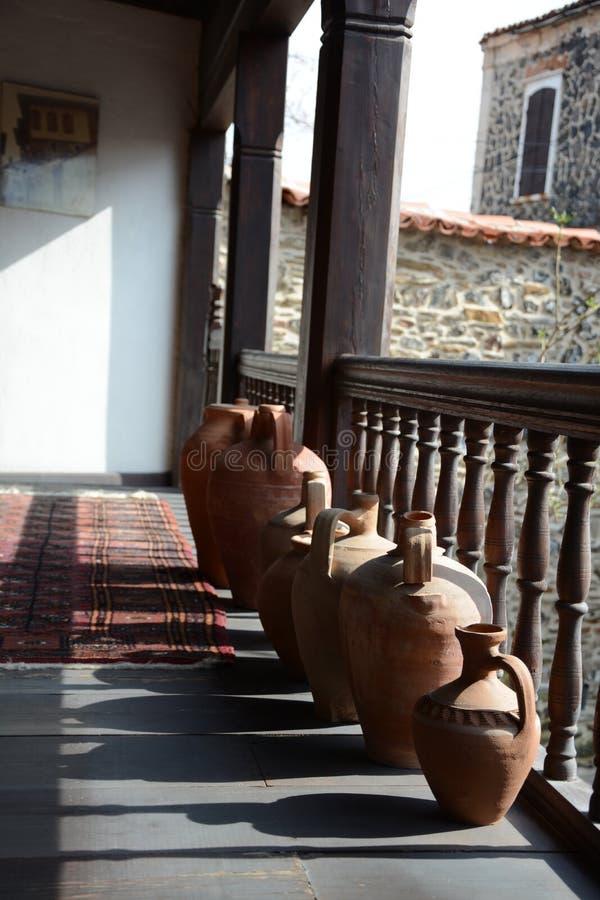 Orange jugs. Old wooden house royalty free stock image