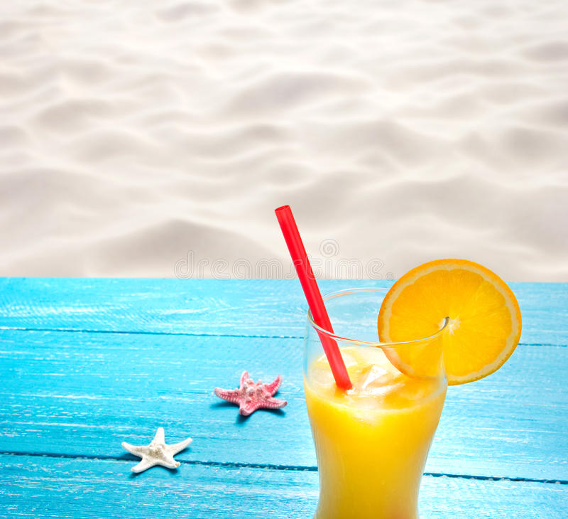Orange juice at the beach. Orange juice at the beautiful beach royalty free stock photography