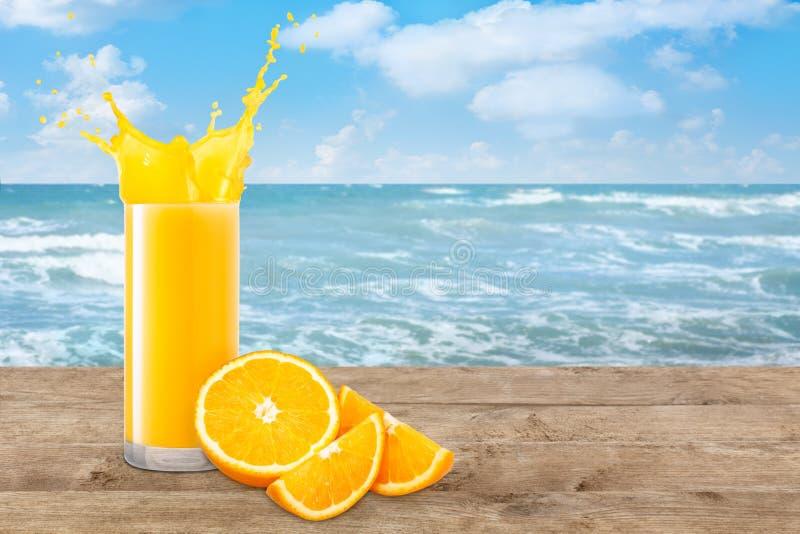 Orange juice on the beach table. Orange juice in glass and fresh orange fruit on the beach table. Orange juice splash. Blurred ocean or sea background. Healthy stock photography