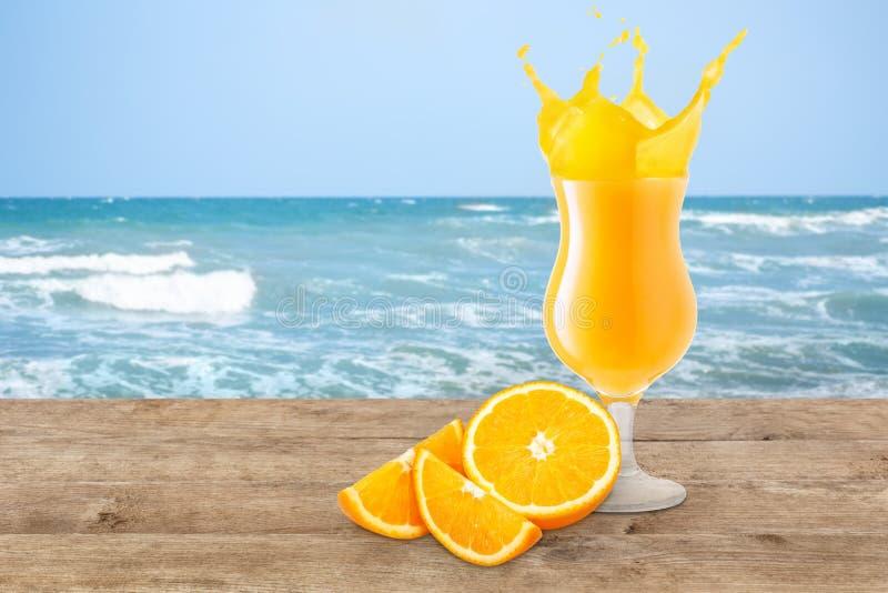 Orange juice on the beach table. Orange juice in glass and fresh orange fruit on the beach table. Orange juice splash. Blurred ocean or sea background. Healthy royalty free stock photography