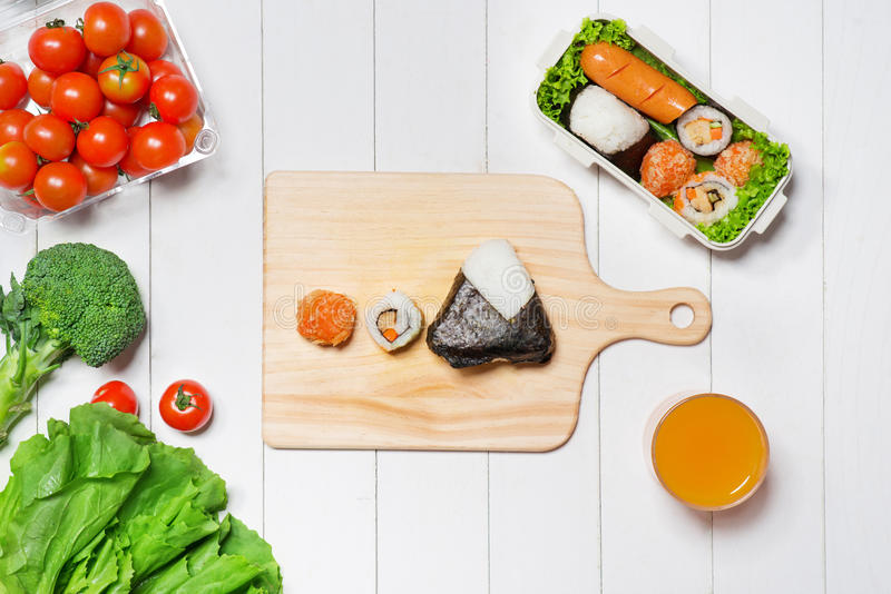 Orange juice and bento box with different food, fresh veggies an royalty free stock photography
